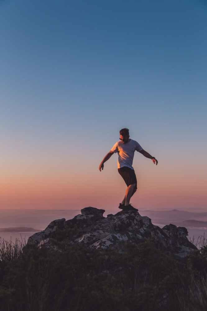 Mann auf Bergspitze - Was ist die beste Methode, um Ausdauer zu steigern?